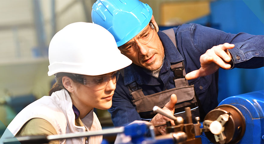 man and woman in hard hats looking at machine